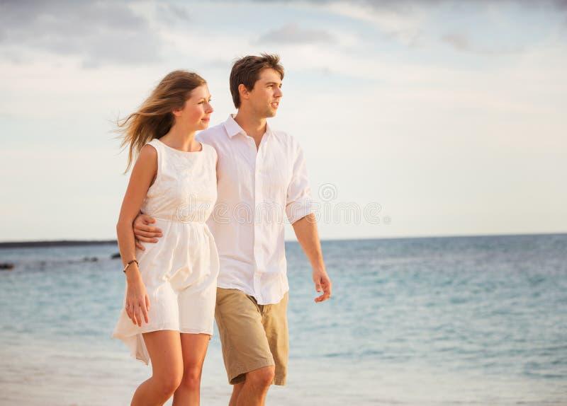 走在海滩的浪漫愉快的夫妇在日落 免版税库存照片