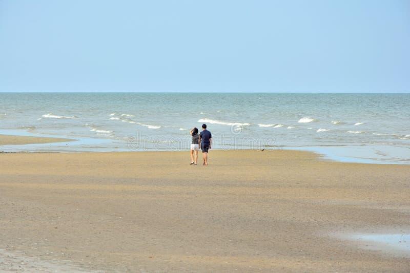 走在海滩的男性和女性夫妇 免版税库存照片
