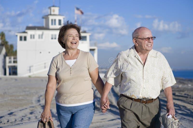 走在海滩的资深夫妇 免版税库存照片