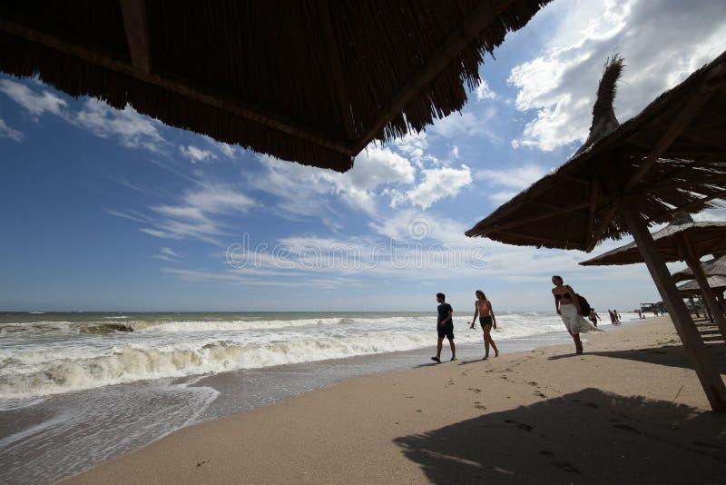 走在海滩的青年人在海在Vama Veche,罗马尼亚 免版税图库摄影