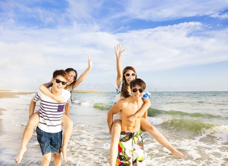 走在海滩的年轻小组享受暑假 免版税库存图片