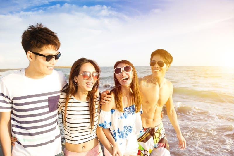 走在海滩的年轻小组暑假 免版税库存照片