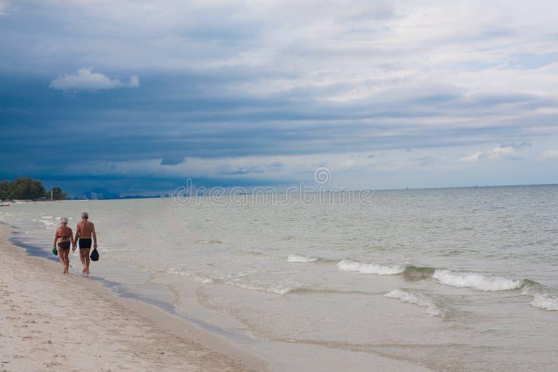 走在海滩风暴的资深夫妇是以后的阴云密布 免版税图库摄影