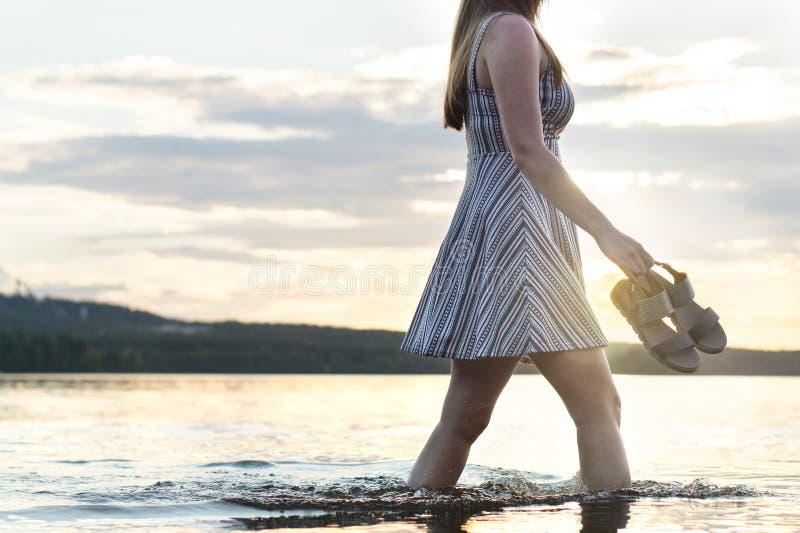 走在湖水中的年轻可爱的妇女在日落 免版税库存图片