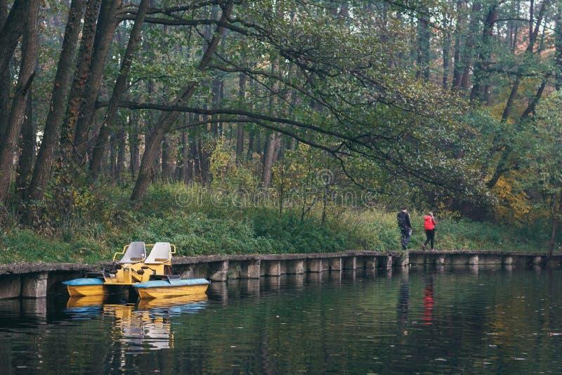 走在湖附近的年轻夫妇在秋天 黄色和蓝色筏在反对秋天森林的湖 库存图片