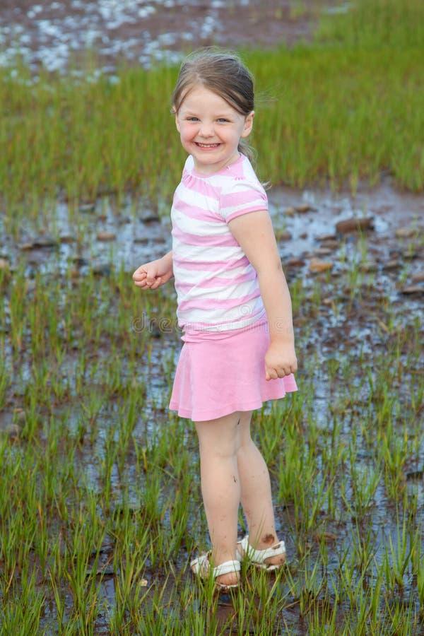 走在湿地面的愉快的女孩 库存图片