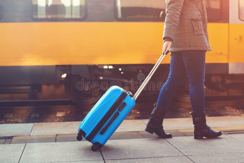 走在火车站的旅游妇女 内部加速的培训旅行 扯拽蓝色行李手提箱的女孩 概念标志旅途映射针塑料红色身分 生活方式,旅行 免版税库存图片