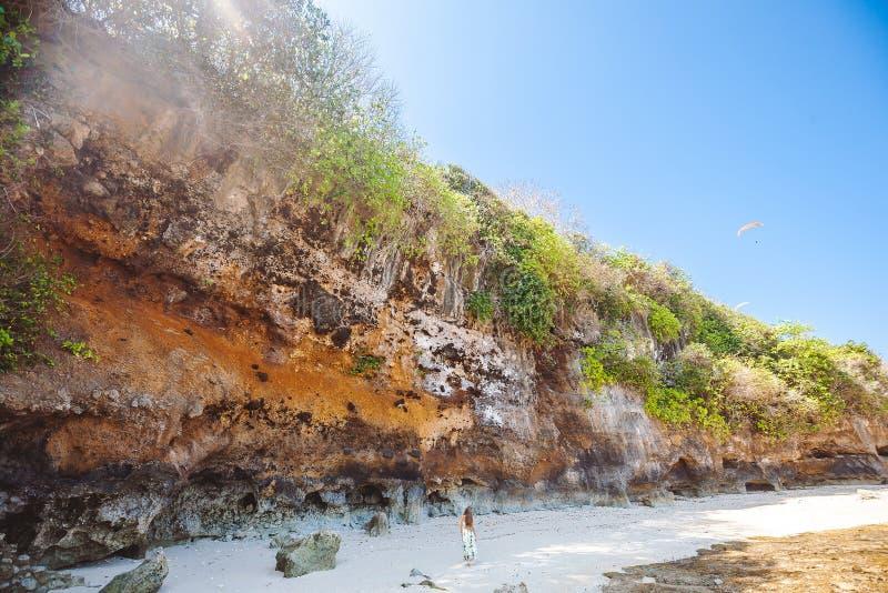 走在热带海滩的妇女在岩石附近 免版税库存图片