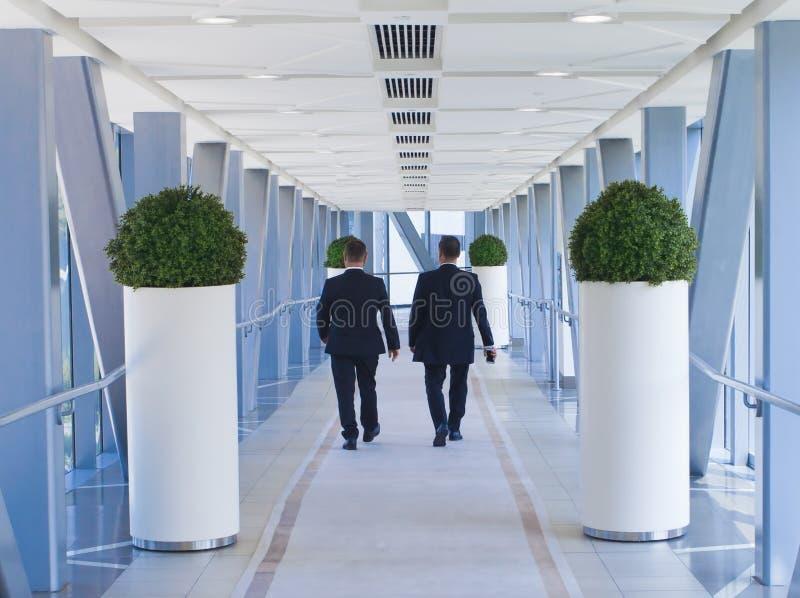 走在现代大厦的两商人人 库存照片