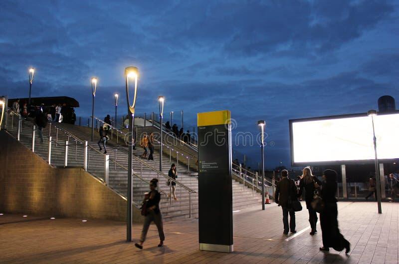走在现代城市街道上的人们在晚上 免版税库存照片
