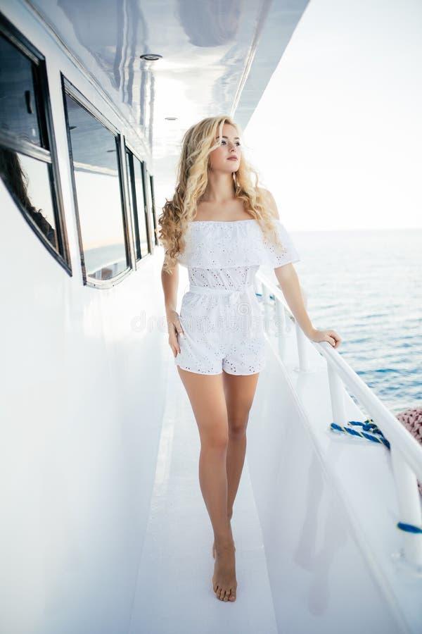 走在甲板的巡航小船假期年轻俏丽的妇女享受从小船的看法 假日目的地的愉快的偶然旅游女孩 免版税库存照片