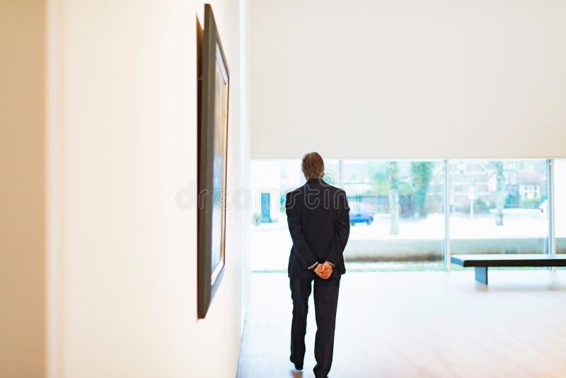 走在白色博物馆室的监护人 库存图片