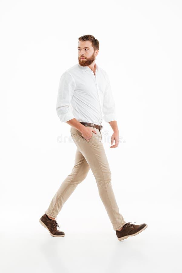 走在白色墙壁的英俊的年轻有胡子的人 图库摄影