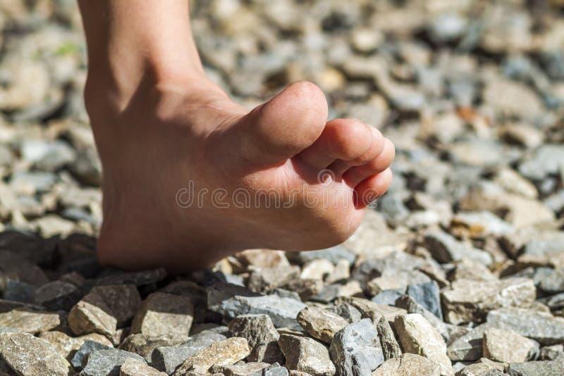 走在石头,户外活动的赤脚特写镜头 图库摄影