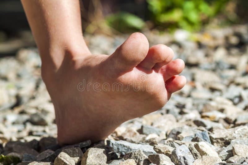 走在石头,户外活动的赤脚特写镜头 免版税库存照片