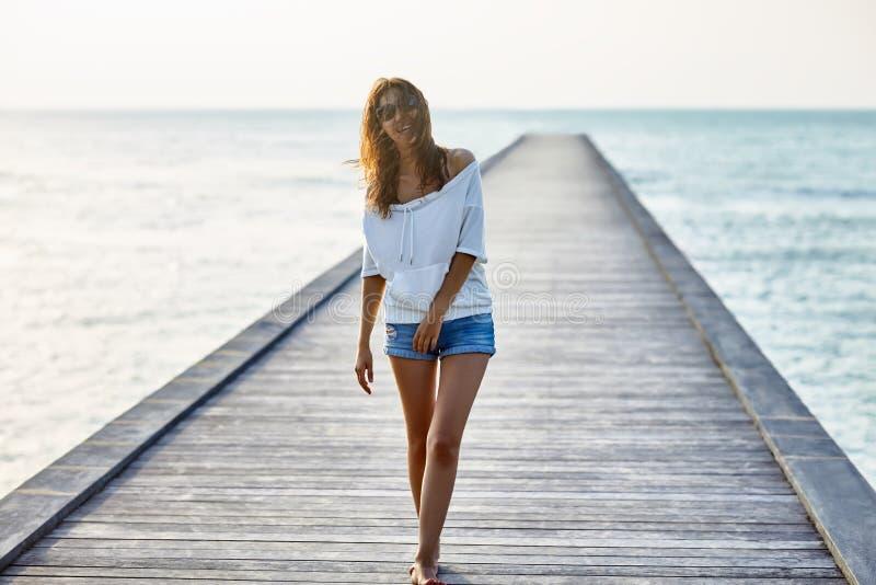 走在码头的年轻美丽的妇女 免版税图库摄影