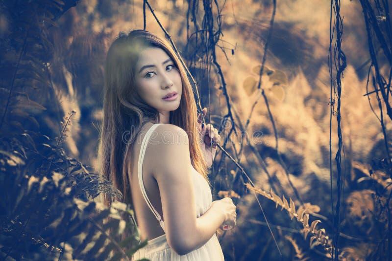 走在神秘的不可思议的深森林里的狭窄女孩 免版税库存图片