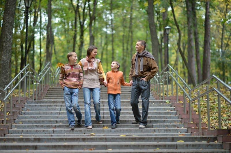 走在秋天公园的四口之家 免版税库存照片