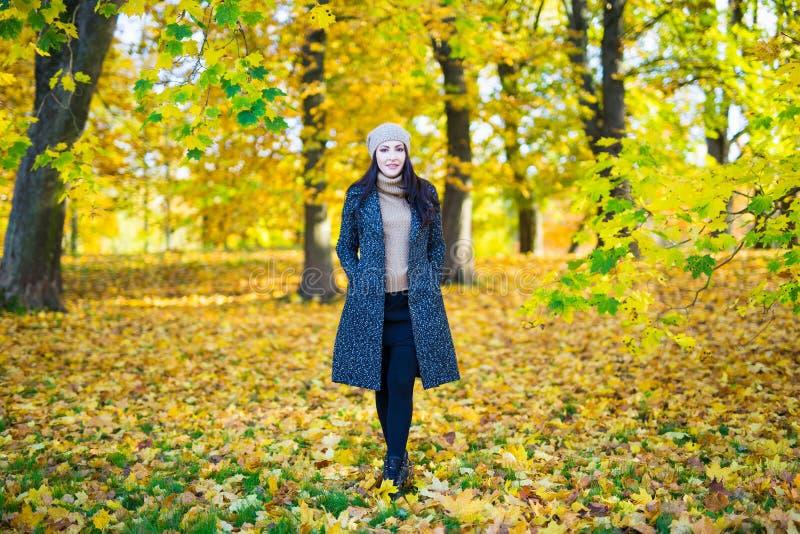 走在秋天公园的少妇全长画象 免版税库存图片