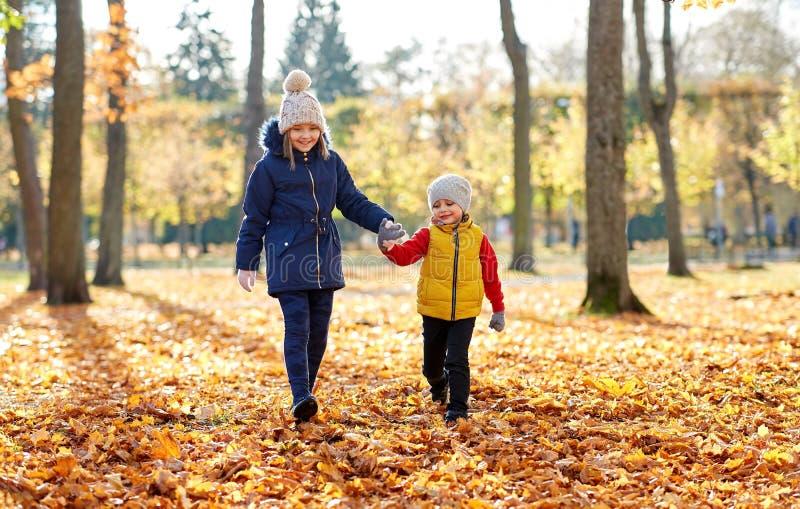 走在秋天公园的愉快的孩子 图库摄影