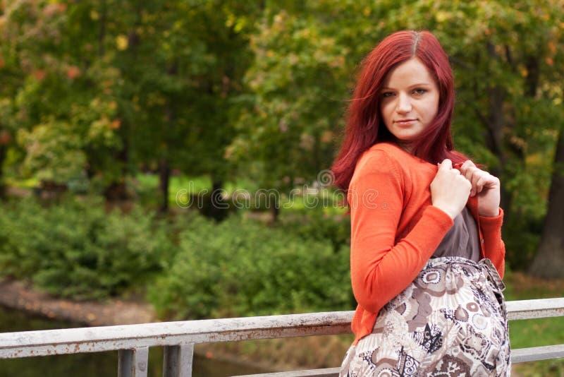 走在秋天公园的美丽的孕妇 免版税库存图片