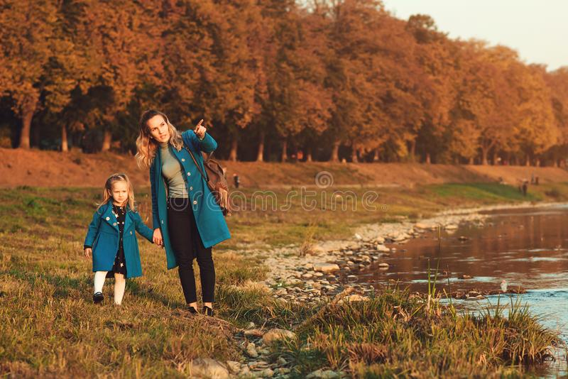 走在秋天时间的河附近的母亲和女儿 愉快的系列 秋天周末露天 享用美丽的autum的家庭 免版税库存图片