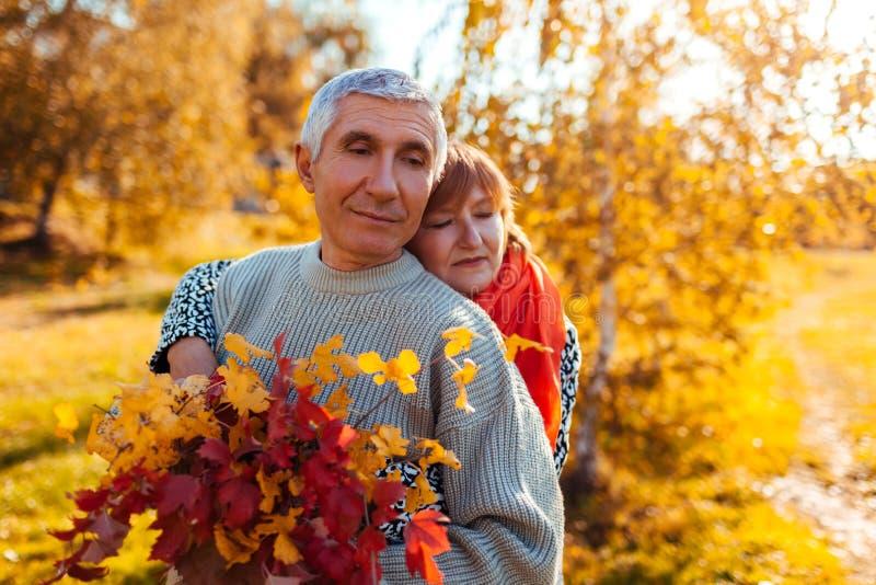 走在秋天森林中年男人和妇女的资深夫妇拥抱和变冷户外 免版税库存照片