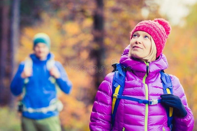 走在秋天森林的男人和妇女愉快的夫妇远足者 免版税库存照片