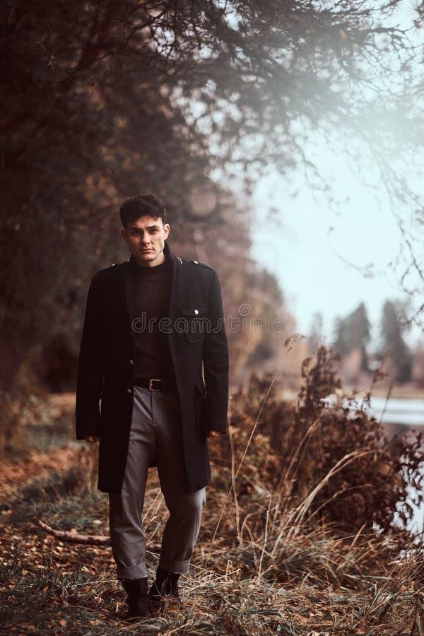 走在秋天森林里的一个英俊的年轻人 免版税库存照片