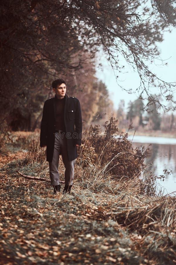 走在秋天森林里的一个英俊的年轻人 库存照片
