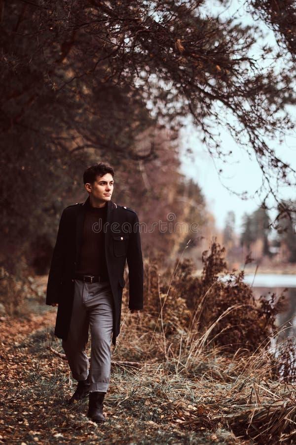 走在秋天森林里的一个英俊的年轻人 库存图片