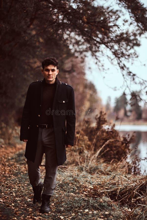 走在秋天森林里的一个英俊的年轻人 免版税图库摄影