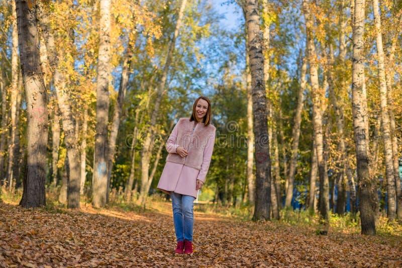 走在秋天森林里的女孩 免版税库存图片