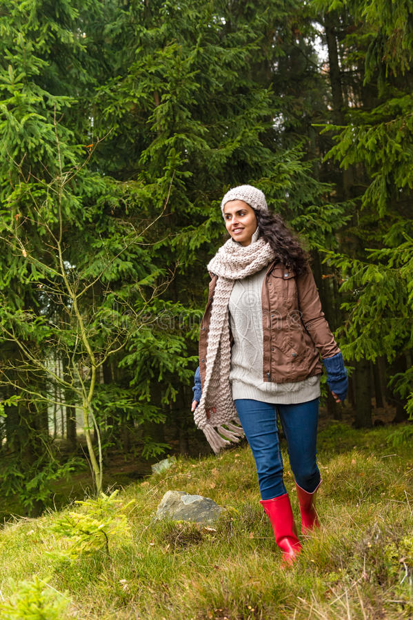 走在秋天森林里的愉快的妇女 免版税图库摄影