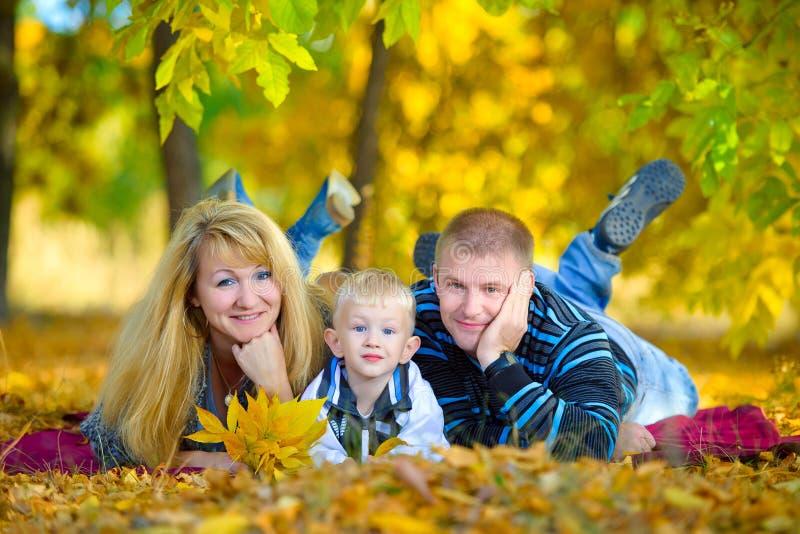 走在秋天自然的愉快的家庭 免版税库存照片