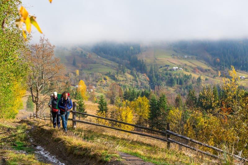 走在秋季森林中的农村足迹的两个远足者 免版税库存照片