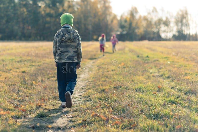 走在笑的孩子后的哀伤的男孩 免版税库存照片