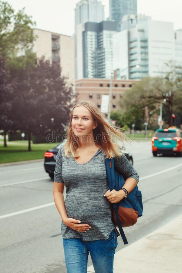 走在繁忙的都市城市的怀孕的年轻白肤金发的白种人妇女 库存图片