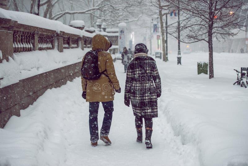 走在纽约曼哈顿街道上的人们在强的雪期间猛冲飞雪和冷气候 免版税图库摄影