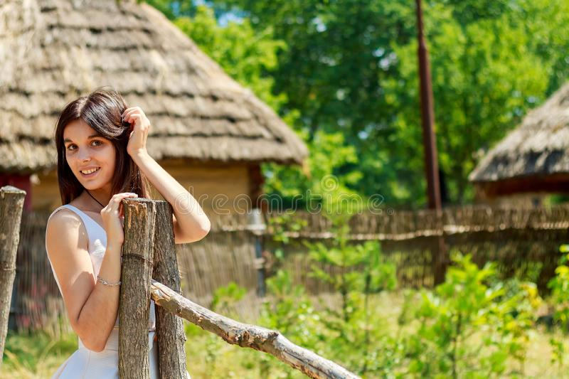 走在绿色公园太阳天的夏天礼服愉快的少年女孩 免版税库存图片