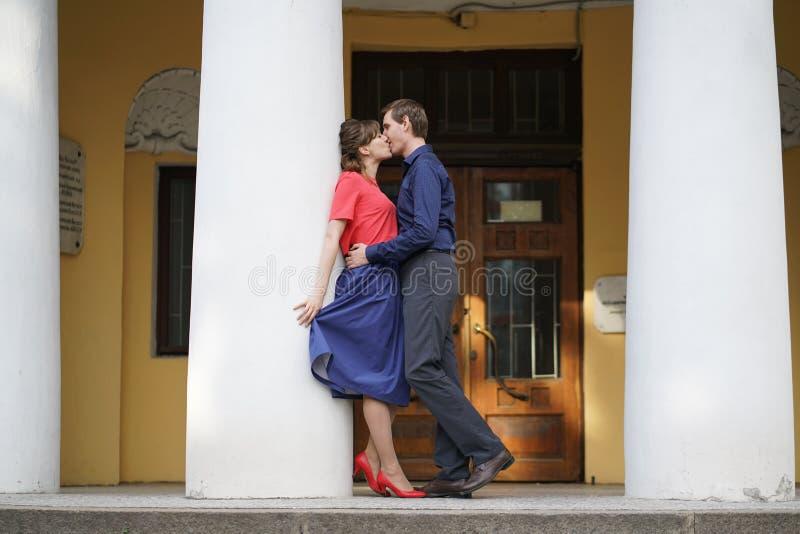 走在绿色夏天公园的俏丽的白种人爱夫妇,有微笑、亲吻和拥抱 免版税库存照片