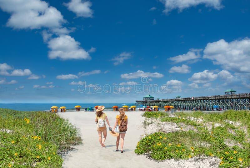 走在美丽的海滩的十几岁的女孩在度假暑假 库存照片