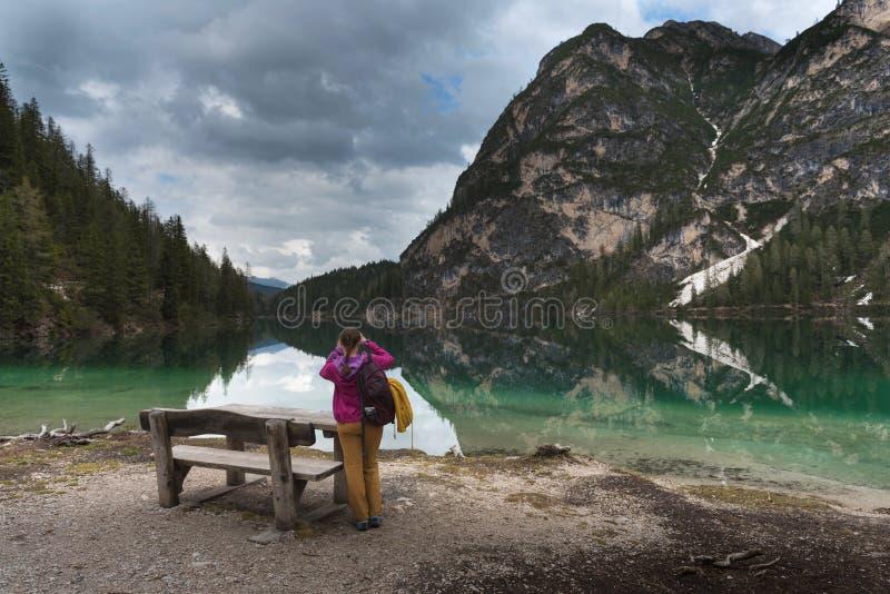 走在美丽的湖Braies,意大利附近的旅游妇女 免版税库存图片