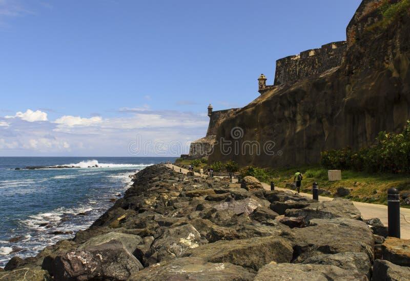 走在老堡垒墙壁下的道路的人们 免版税库存图片