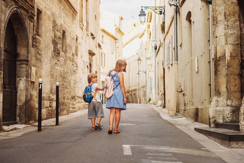 走在老欧洲镇街道上的小组两个孩子  图库摄影