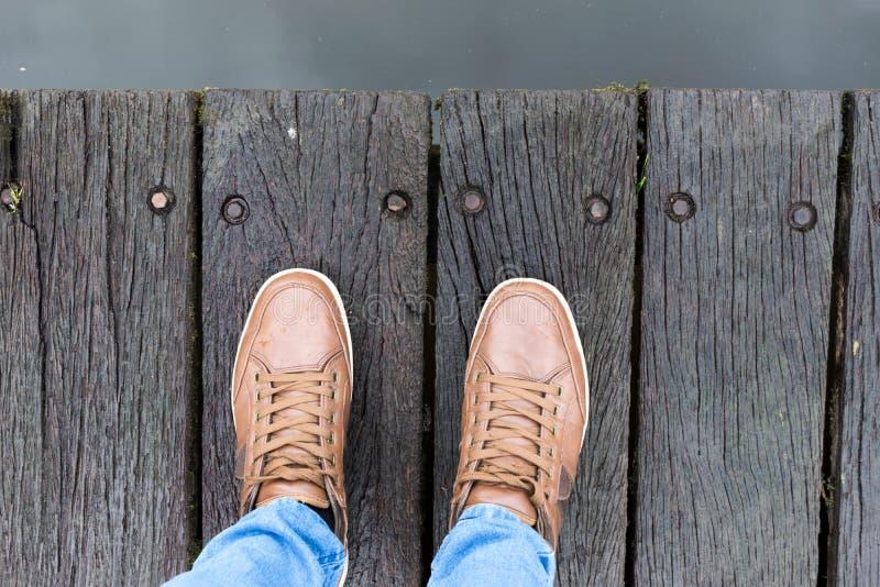 走在肮脏的木顶视图的运动鞋鞋子 库存图片