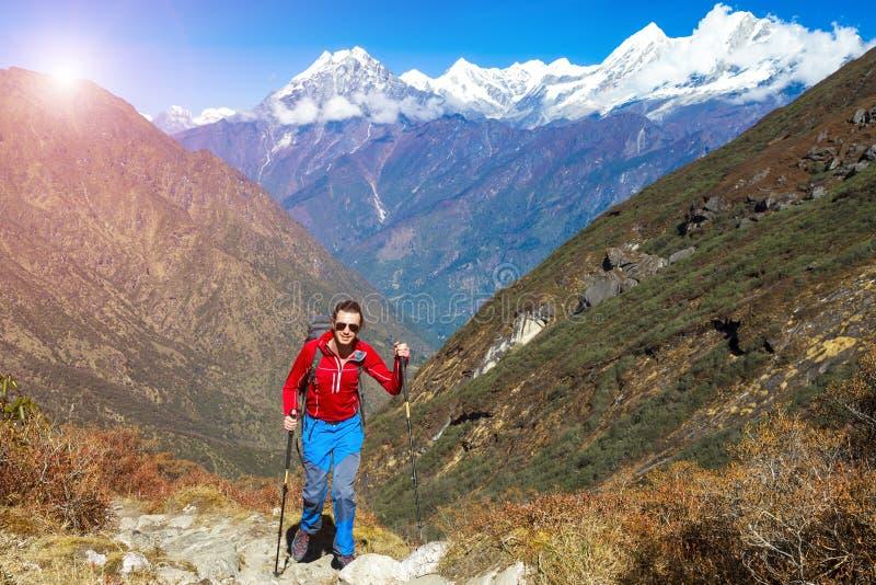 走在背景的山行迹太阳的年轻远足者 免版税库存图片
