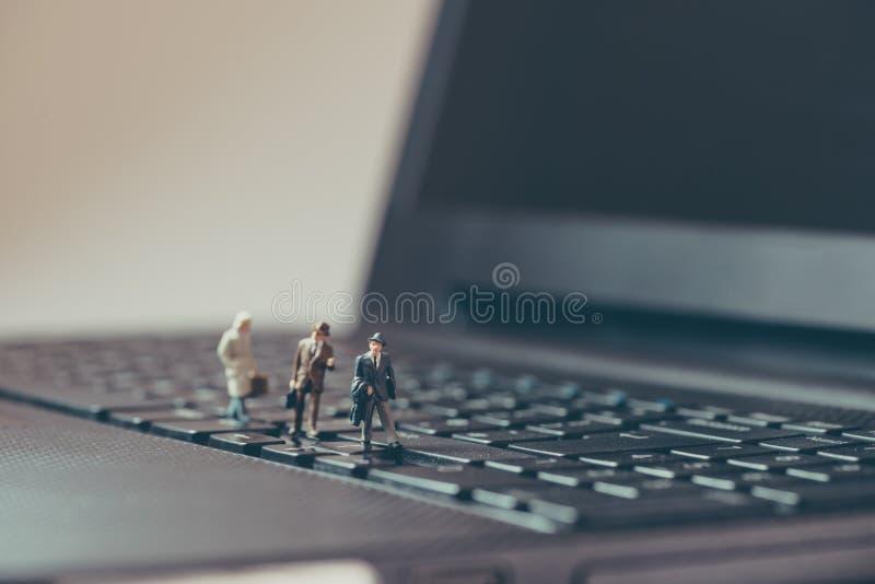 走在膝上型计算机的微型商人 免版税图库摄影