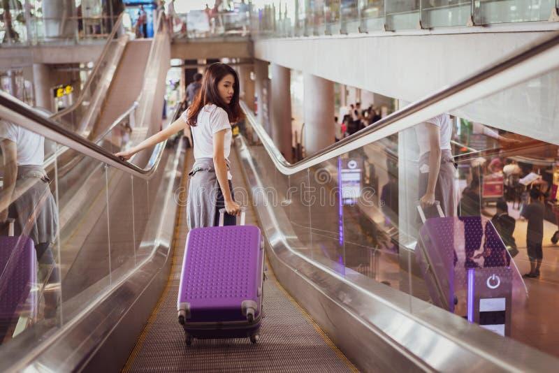 走在自动扶梯的亚裔妇女旅客到飞机 免版税图库摄影