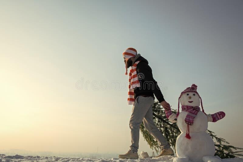 走在蓝天的人和雪人 免版税库存图片